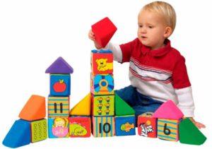 ребенок собирает башню из кубиков