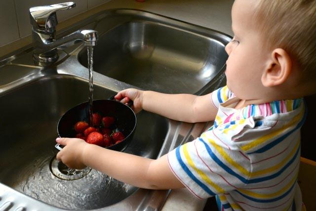 ребенок моет ягоды