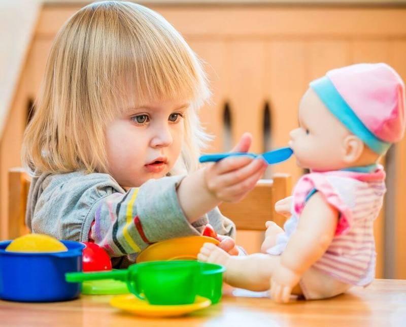 ребенок кормит куклу
