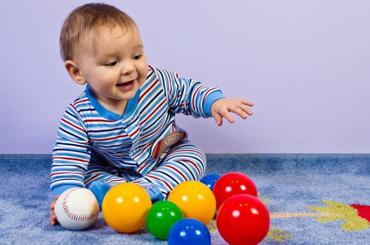малыш играет с мячиками